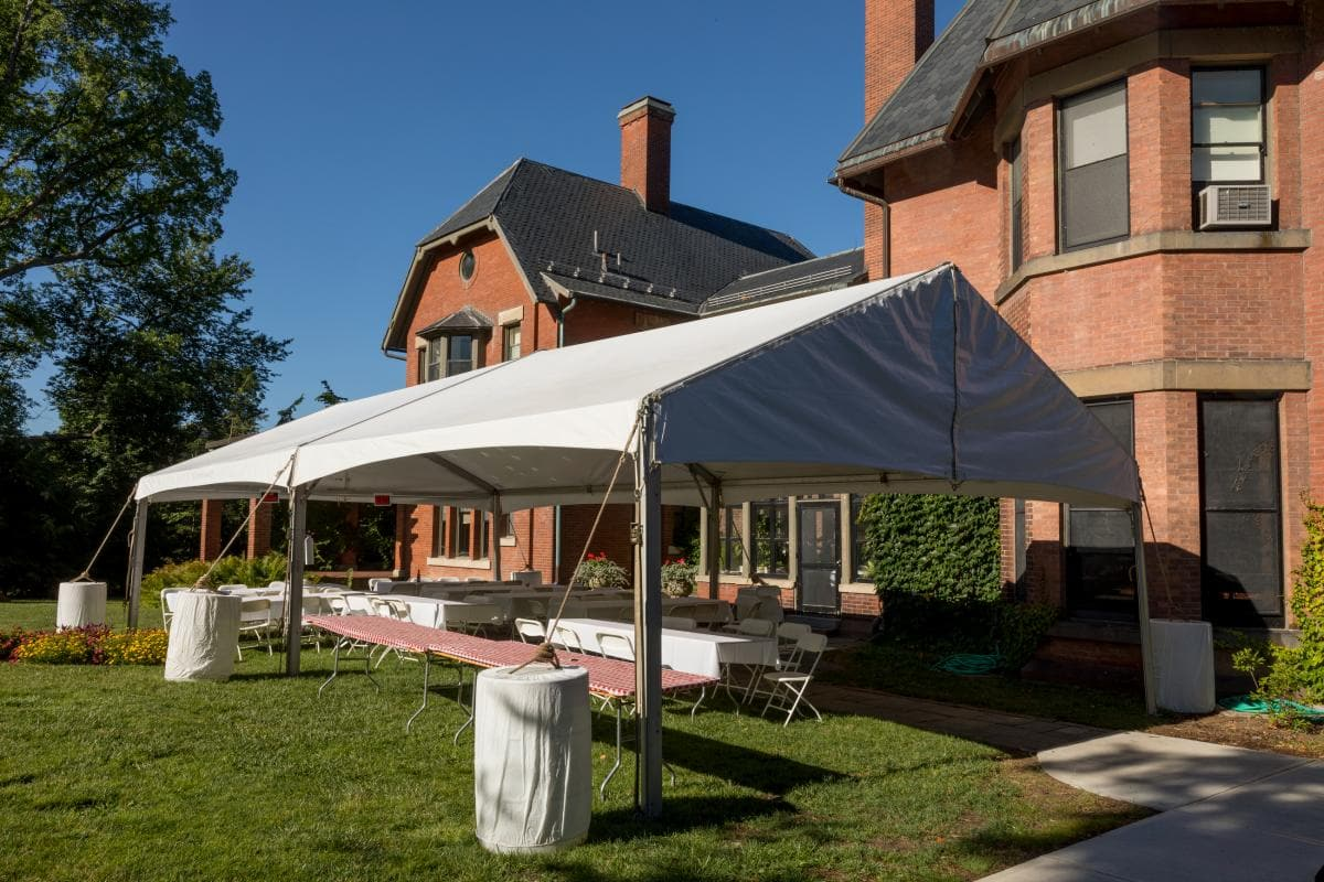 A.D. White House patio set up with tent and several tables for a summertime seated dinner.