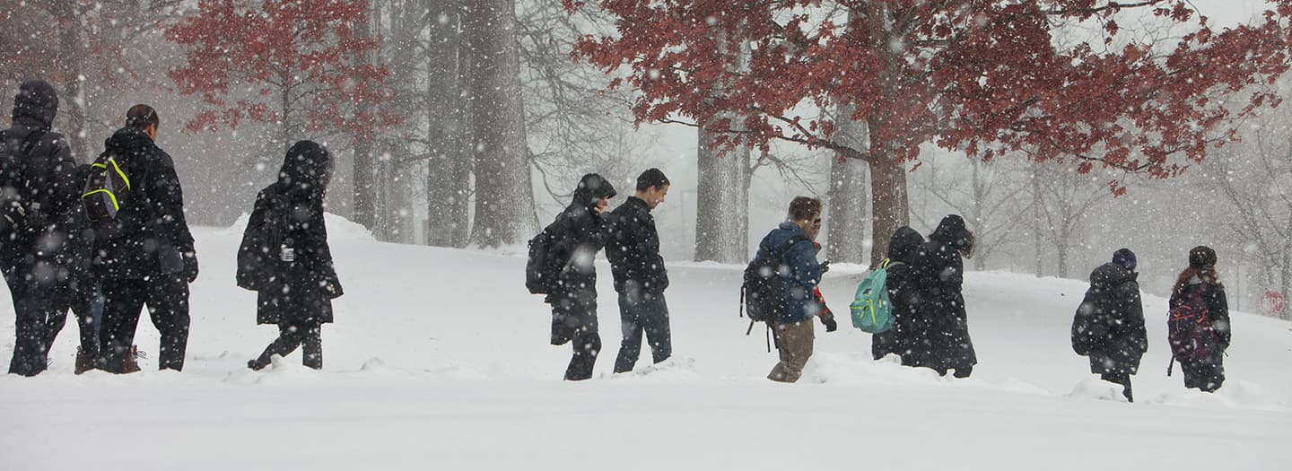 students walking through snow on Cornell's campus, in front of Andrew Dickson White House