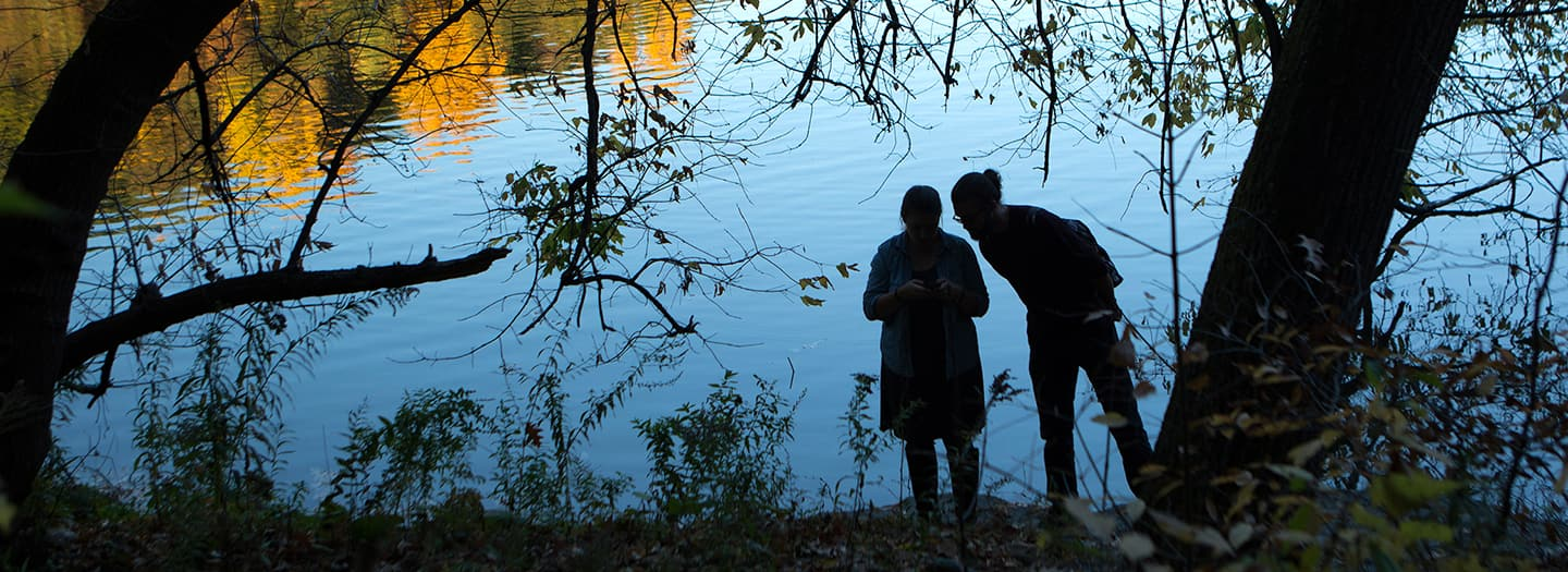 two silhouetted figures surrounded by trees in front of a lake