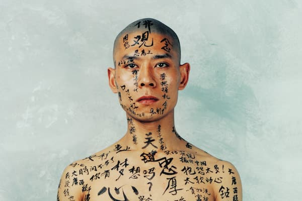 "Zhang Huan, ""1/2,"" 1998, Beijing, China, an artwork featuring a shirtless man with Chinese calligraphy painted on his skin"